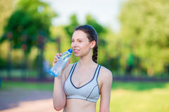 Young woman drinking water after running outside. Female fitness model training outside in the park. Concept of healthy Stock Photography
