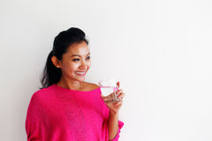 Young woman drinking water and standing against a white wall Stock Photo