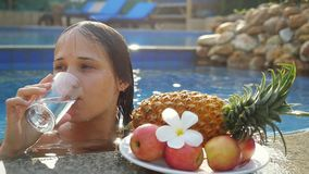 Young woman drinking water while sunbathing in the pool at plate with fruits and plumeria flower in slow motion stock footage