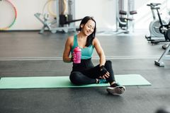 Young woman drinking water in gym, Royalty Free Stock Photography