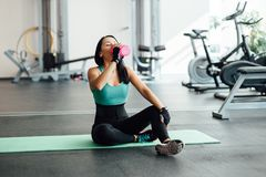 Young woman drinking water in gym, Royalty Free Stock Photo