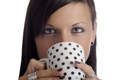 Young woman drinking from a white & black cup Royalty Free Stock Photos