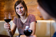 Young woman drinking wine with friend. Portrait of happy young women drinking wine with friend in bar Stock Photography