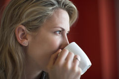 Young woman drinks breakfast coffee royalty free stock image