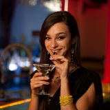 Young woman drinks a cocktail in night club Royalty Free Stock Image