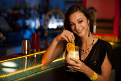 Young woman drinks a cocktail in night club. Girl drinks a cocktail in night club Royalty Free Stock Image
