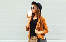 Young woman drinks coffee in black round hat, sunglasses royalty free stock photo