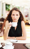 Young woman drinks coffee in cafe Royalty Free Stock Photos