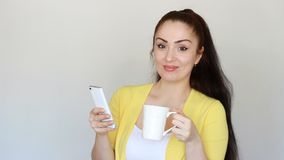 Young woman drinks a coffee from a cup and using internet application, looks on mobile app on smartphone screen and. Smiles. Girl holds a cell phone in his hand stock footage