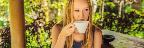 Young woman drinks coffee Luwak in the gazebo BANNER, long format royalty free stock image