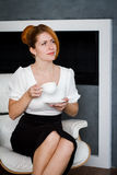 Young woman drinks coffee at office. Attractive business woman sitting at office desk, holding a cup of coffee, she is relaxing and looking away Stock Photo