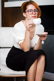 Young woman drinks coffee at office Stock Photos