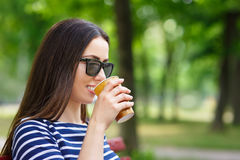 Young woman drinks coffee outdoors stock photos