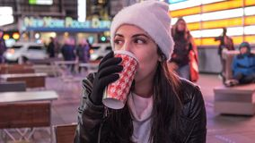 Young woman drinks a cup of coffee in the streets of New York