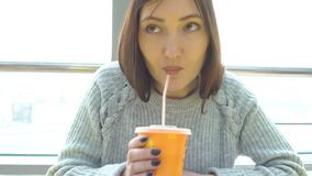 Young woman drinks freshly squeezed juice in a cafe.  stock footage