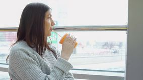 Young woman drinks freshly squeezed juice in a cafe, looking out the window stock images