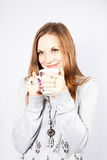 Young woman drinks a hot drink from a cup Stock Photo