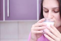 Young woman drinks milk from the case in the evening because of her health royalty free stock photography
