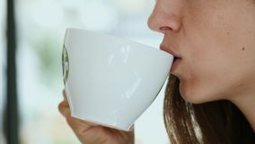 Young woman drinks morning coffee with cookie. Closeup of young woman enjoy drinking hot coffee from white cup and eating cookie with feeling good in cafe. Young stock footage
