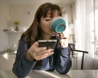 A young woman drinks from a mug on the background of the kitchen, uses her phone royalty free stock images