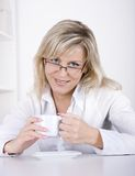 The young woman drinks tea or coffee Royalty Free Stock Image