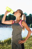 Young woman drinks a water. Young attractive woman drinks a water from bottle and enjoys a rest outdoors, soft focus background Stock Image