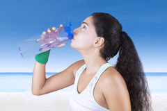 Young woman drinks water at the beach Royalty Free Stock Photos