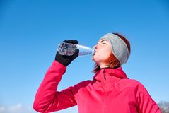 Young woman drinks water from bottle after jogging in winter cit royalty free stock image