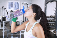 Young woman drinks water in fitness center. Portrait of young woman resting and drinking water on the bottle in fitness center with winter background on the Stock Photos