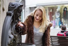 Young woman drinks water. From a fountain Stock Images