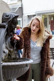 Young woman drinks water. From a fountain Stock Photography