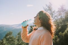 Young woman drinks water in the middle of the mountain stock images
