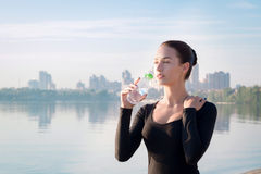 Young woman drinks water at morning river and city backround Royalty Free Stock Photos