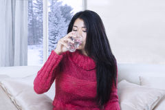 Young woman drinks water on sofa Stock Photo