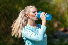 Woman drinks water in a sport dress. Young woman drinks water in a sport dress Royalty Free Stock Photo