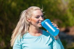 Woman drinks water in a sport dress. Young woman drinks water in a sport dress Stock Photography
