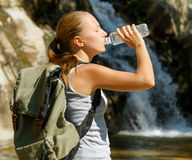 Young woman drinks water by waterfall Royalty Free Stock Photography