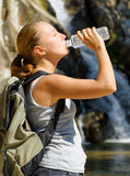 Young woman drinks water by waterfall Stock Photography