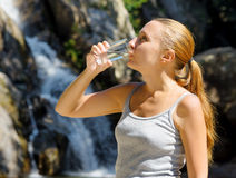 Young woman drinks water by waterfall Royalty Free Stock Photo