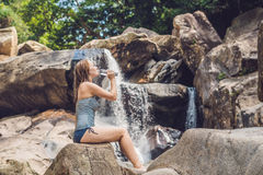 Young woman drinks water on a waterfall background Royalty Free Stock Photos