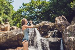 Young woman drinks water on a waterfall background Stock Image