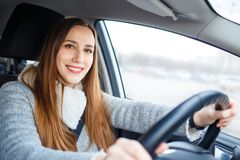 Young woman drive a car in winter Stock Photos