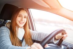 Young woman drive a car in winter. Smiling european woman steering wheel inside a car Royalty Free Stock Image