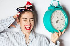 Young woman driven crazy by alarm clock Royalty Free Stock Image