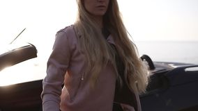 Young woman driver in beige leather jacket with long hair and stylish sunglasses opening the door of her cabriolet car. At a stop during a trip to look around stock footage