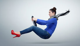 Young woman driver car with a wheel on background Stock Photo