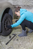 Young woman driver changes car tyres Stock Image