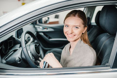 Young woman driver sitting in new car with key in hands Stock Image