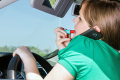 Young woman driving , applying lipstick and speaking on her smart phone royalty free stock image