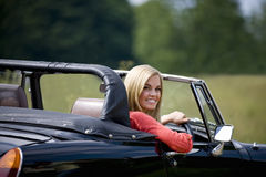 A young woman driving a black sports car Royalty Free Stock Photography